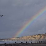 A rainbow develops as sun shines on the hillsides by Scripps Pier in La Jolla.